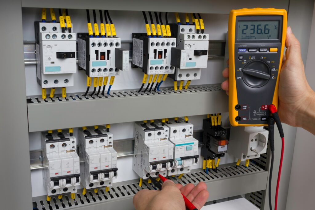 Electrician at work (measuring voltage in electrical cabinet).