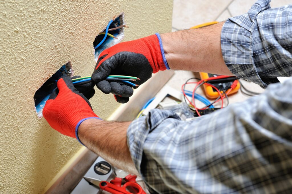 Electrician technician at work pulls the cables installed in a residential electrical system